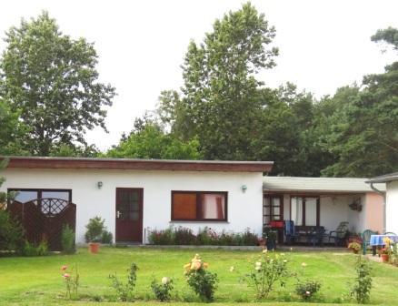Blick auf das Ferienhof-Gästehaus mit einem Doppelbettzimmer sowie einem Einbettzimmer und einer überdachten Sitzfläche vor dem Eingang