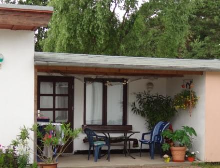 Blick auf die Zimmervermietung Ferienhof Am Kiefernwald mit einem Doppelbettzimmer sowie einem Einbettzimmer und einer überdachten Sitzfläche vor dem Eingang